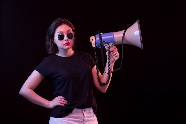 Young woman in black t-shirt holding megaphone Free Photo