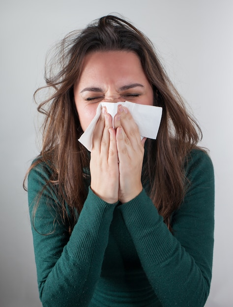 Young woman blowing her nose with paper tissue. Premium Photo