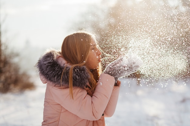 Young woman blowing snow from hands Free Photo