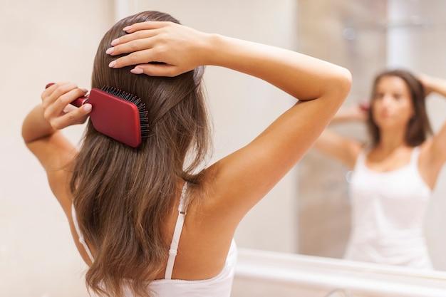 거울 앞에서 건강 한 머리를 솔 질하는 젊은 여자 무료 사진