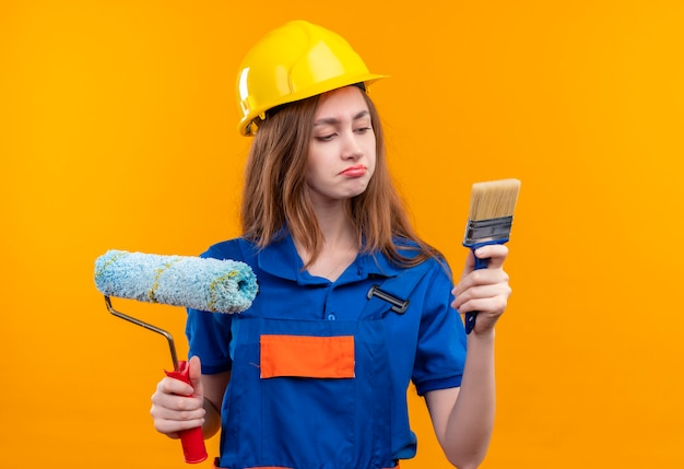 Young woman builder worker in construction uniform and safety helmet holding brush and paint roller looking at brush with skeptic expression standing over orange wall Free Photo