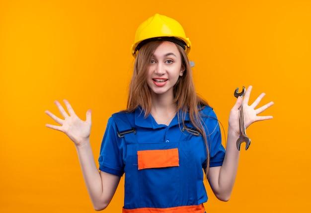 Operaio del costruttore della giovane donna in uniforme della costruzione e chiave della tenuta del casco di sicurezza che solleva le mani nella resa sorridente che sta sopra la parete arancio Foto Gratuite