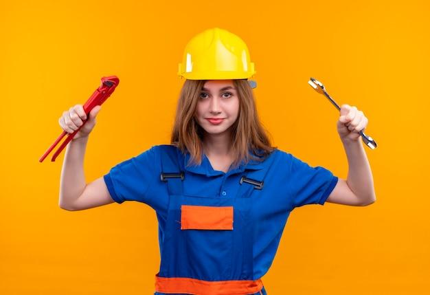 Operaio del costruttore della giovane donna in uniforme della costruzione e casco di sicurezza che tiene le chiavi in mani alzate che sembrano fiducioso in piedi sopra la parete arancione Foto Gratuite