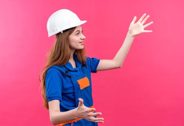Operaio del costruttore della giovane donna in uniforme della costruzione e casco di sicurezza che osserva da parte con il sorriso sul fronte che gesturing con le mani che stanno sopra la parete rosa Foto Gratuite