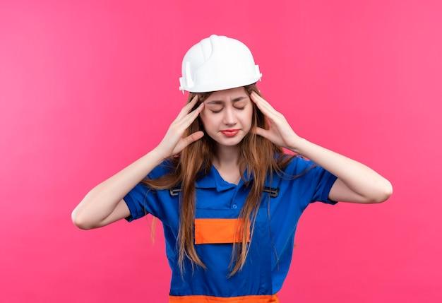 Operaio del costruttore della giovane donna in uniforme da costruzione e casco di sicurezza che sembra stanco e sovraccarico di lavoro con mal di testa in piedi sopra il muro rosa Foto Gratuite