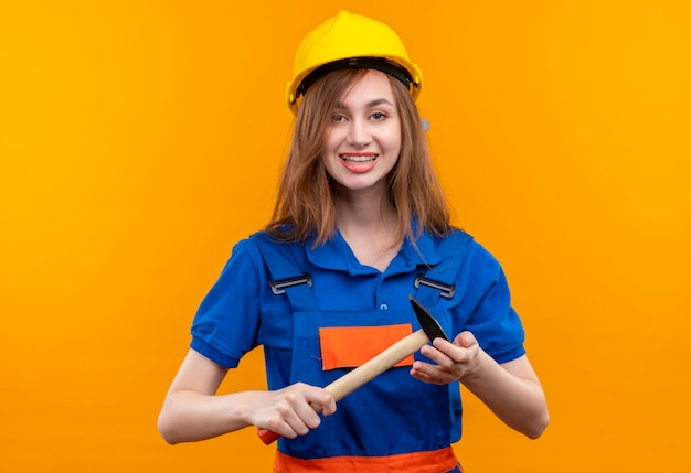 Young woman builder worker in construction uniform and safety helmet positive and happy smiling holding hammer standing over orange wall Free Photo