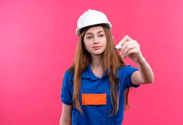 ピンクの壁の上に立っているペンで空中で何かを書き込もうとしている建設制服と安全ヘルメットの若い女性ビルダー労働者 無料写真