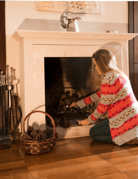 Young woman burning fireplace with matchstick at home Free Photo