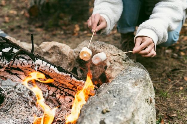 Giovane donna che brucia marshmallow nel fuoco di campo in inverno Foto Gratuite