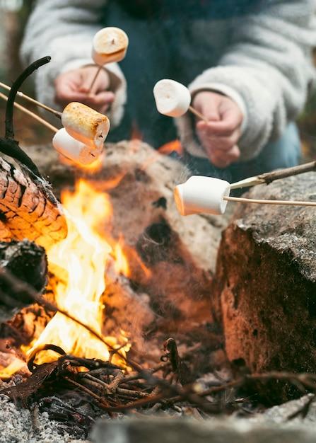 Giovane donna che brucia marshmallow nel fuoco di campo Foto Gratuite