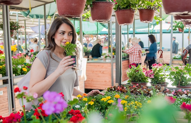 Young woman buying flowers at a garden center. My favorite flowers. Woman looking at flowers in a shop. Portrait of a smiling woman with flowers in plant nursery Free Photo