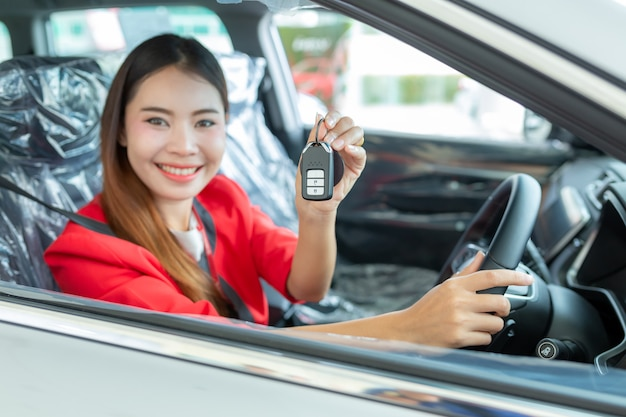 Young woman buys a car with receiving the keys of her new car, Premium Photo