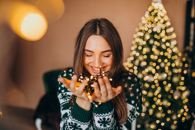 Young woman by the christmas tree with christmas glowing lights Free Photo