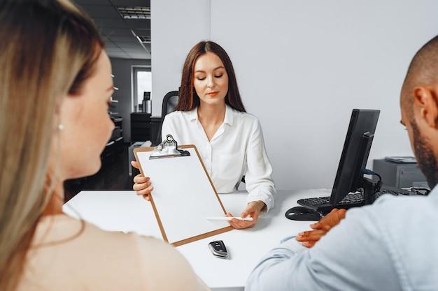 彼女のオフィスで車のバイヤーのカップルに契約を示す若い女性の車の売り手 Premium写真