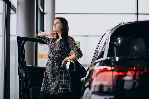 Young woman in a car showroom choosing a car Free Photo