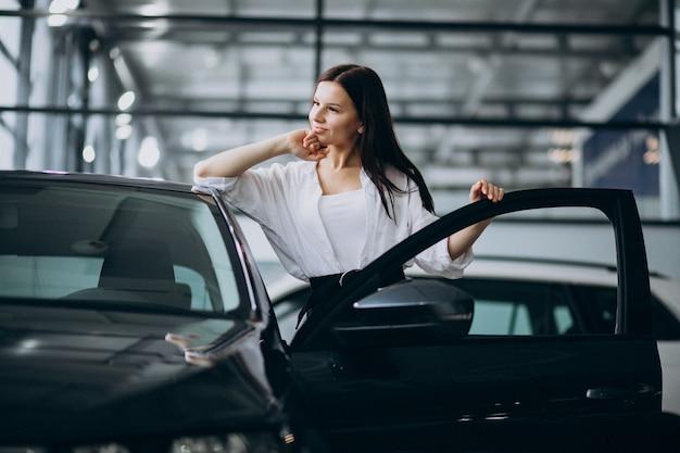 Young woman in a car showroom choosing a car Free Photo