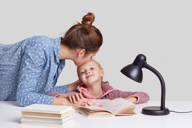 Young woman cares of her child, kisses daughter in forehead, praises her to study well, explains material, read books and prepare for lessons at school, isolated on white. studying concept Free Photo