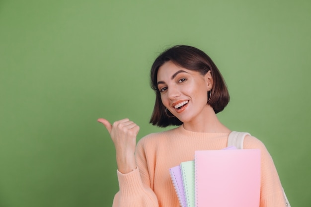 Young woman in casual peach sweater isolated on green olive color wall Free Photo