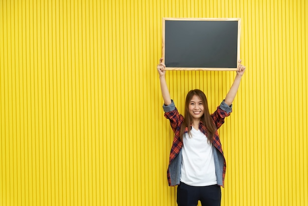Young woman in casual show an empty blackboard on yellow wall with smiling. Premium Photo