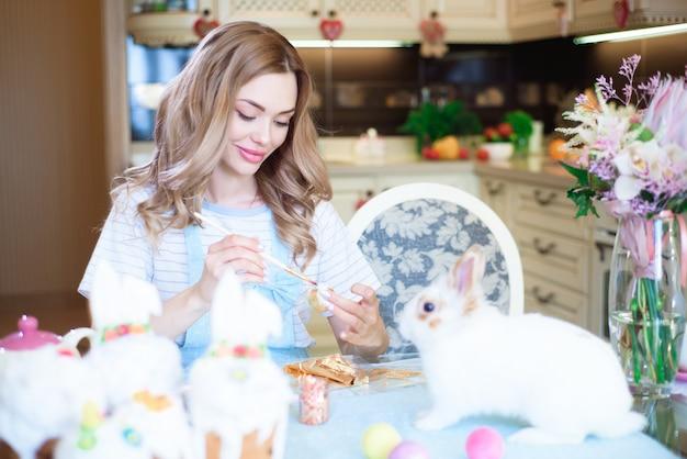 イースターを祝って、ブラシで卵を描く若い女性。 Premium写真