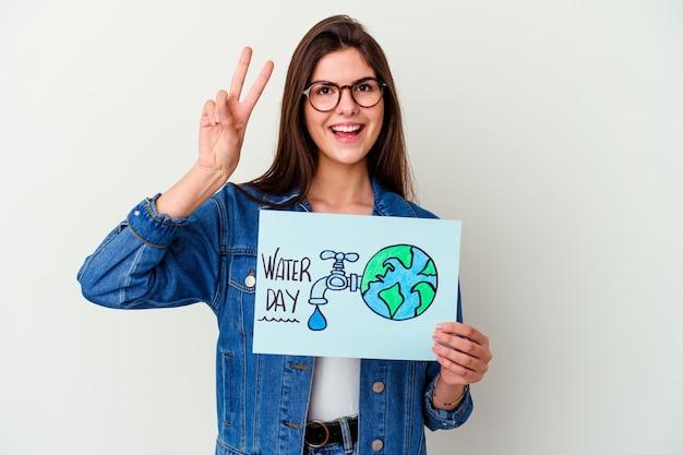 ピンクの壁に隔離された世界水の日を祝う若い女性が指で2番目を示しています Premium写真