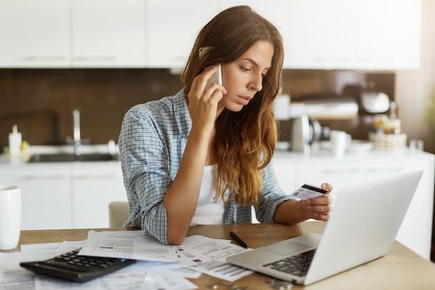 Молодая женщина проверяет свой бюджет и делает налоги Бесплатные Фотографии