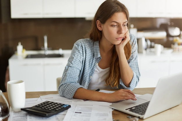 Young woman checking her budget and doing taxes Free Photo