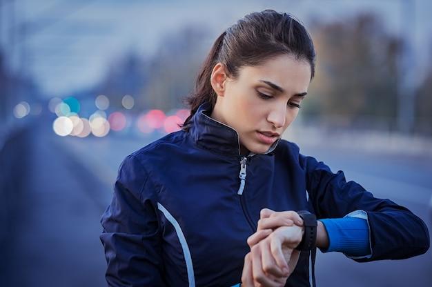 通りを走った後の時間をチェックする若い女性 Premium写真