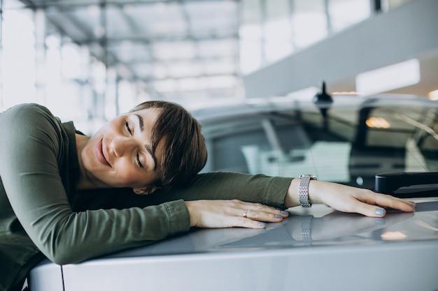Молодая женщина выбирает автомобиль в автосалоне Бесплатные Фотографии