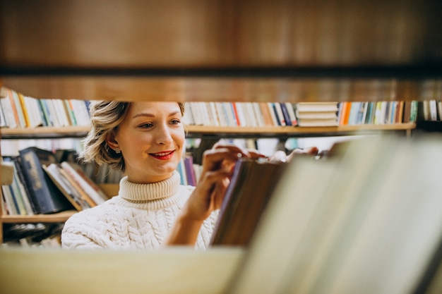 Young woman choosing book at the library Free Photo