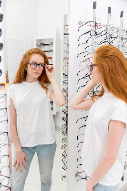 Young woman choosing eyeglasses and looking at mirror in optica Free Photo