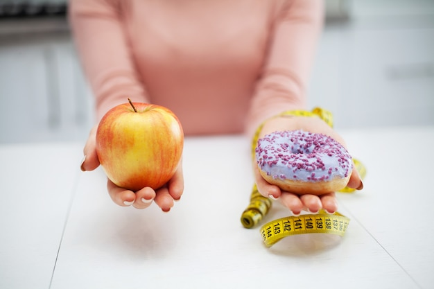 Young woman choosing between fruits and sweets Premium Photo