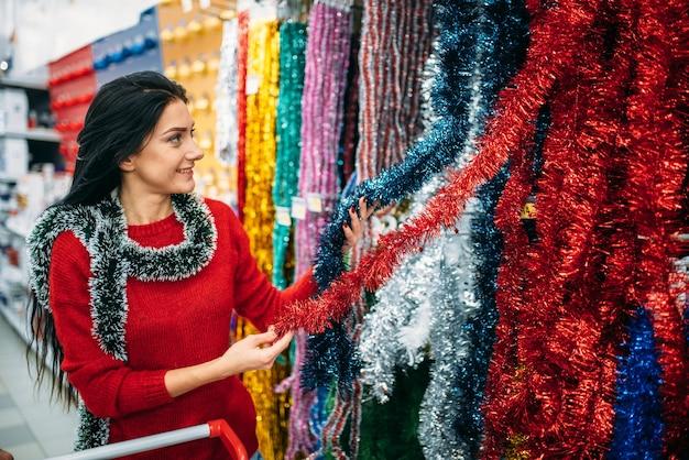 Молодая женщина, выбирая праздничную пушистую гирлянду Premium Фотографии