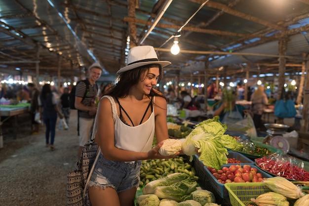 Young woman choosing vegetables on market girl shopping on street bazaar Premium Photo
