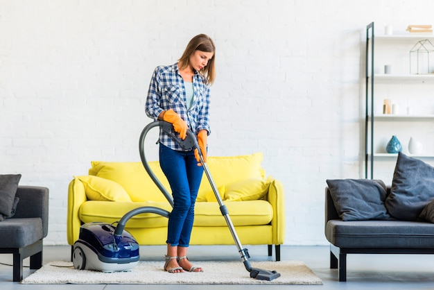Young woman cleaning carpet with vacuum cleaner in front of yellow sofa Free Photo