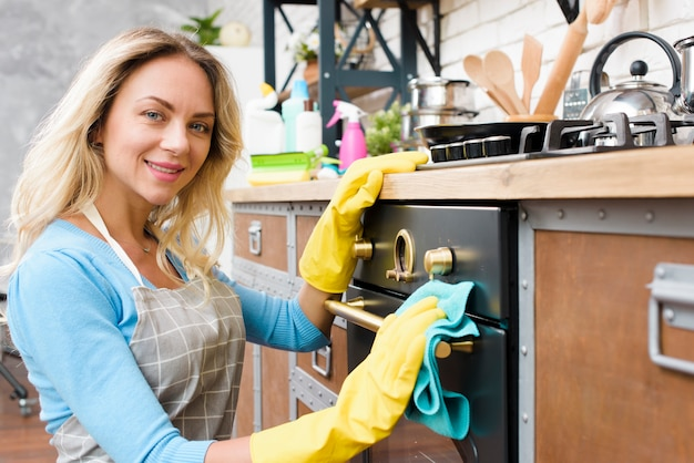 Young woman cleaning in kitchen looking at camera Free Photo