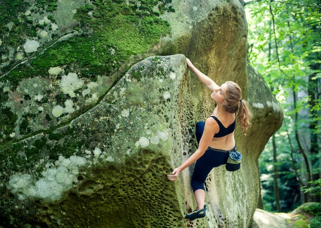 Young woman climbing on large boulders outdoor summer day Premium Photo