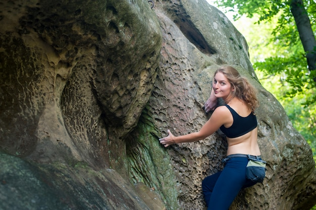 Young woman climbing on large boulders outdoor Premium Photo