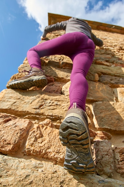 Young woman climbing on a stone wall Premium Photo
