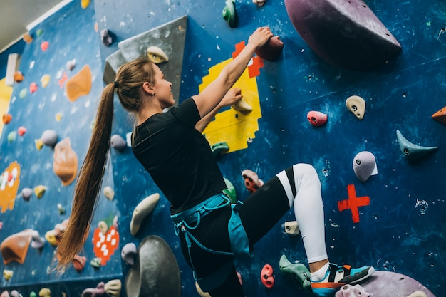 Young woman climbing a tall, indoor, man-made rock climbing wall Free Photo
