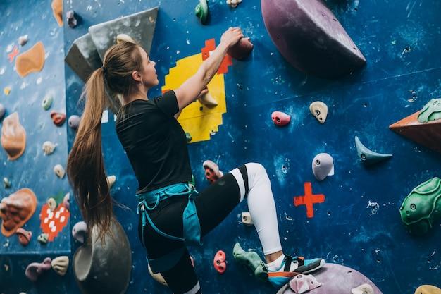 Giovane donna arrampicata su una parete di arrampicata alta, coperta, artificiale Foto Gratuite