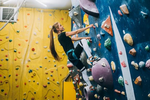Giovane donna arrampicata su una parete di arrampicata su roccia alta, coperta, artificiale Foto Gratuite