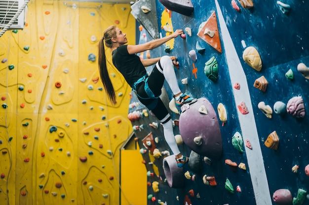 Young woman climbing a tall, indoor, man-made rock climbing wall Free Photo