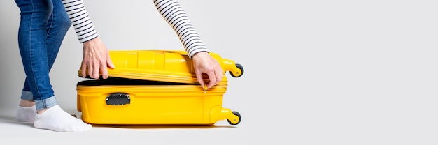 Young woman closes a suitcase on a light background. vacation and travel concept. banner Premium Photo