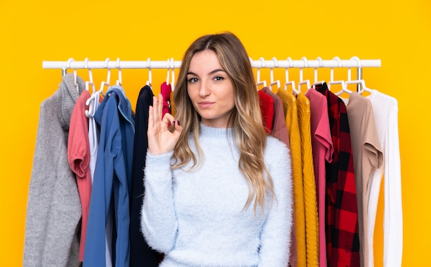 Young woman in a clothing store over isolated yellow wall showing an ok sign with fingers Premium Photo