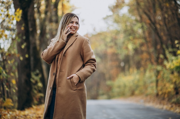 Young woman in coat standing on the road in an autumn park Free Photo