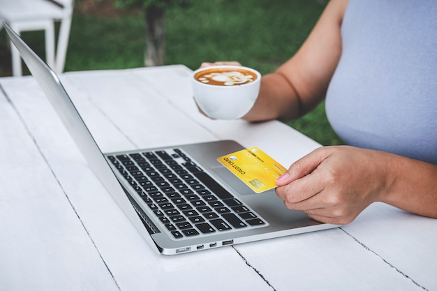 Young woman consumer holding credit card and typing on laptop for online shopping and payment make a purchase on the internet, online payment, networking and buy product technology Premium Photo