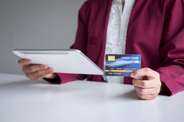 Young woman consumer holding digital tablet, credit card and typing for online shopping and payment make a purchase on the internet, online payment, networking and buy product technology Premium Photo
