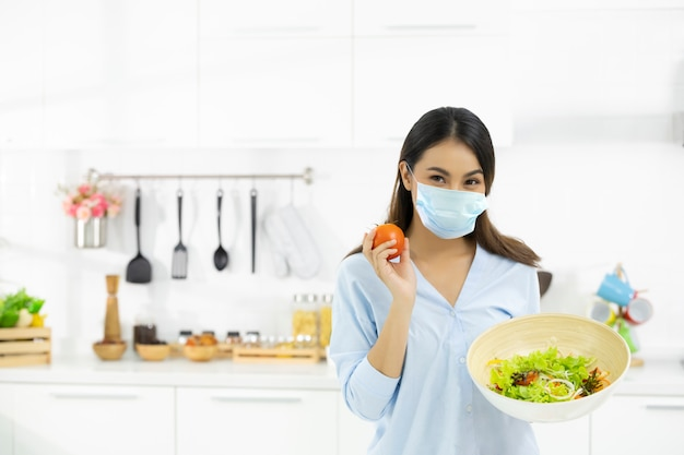 Young woman cooking delicious food in the kitchen and wearing face protection mask to anti saliva, cough. stay at home during the covid-19 self-quarantine 14 days. Premium Photo