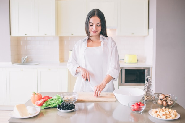 Young woman cooking in kitchen. she stands and cuts vegetable. Premium Photo